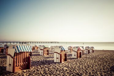 Germany, Niendorf, view to Timmendorfer Strand with hooded beach chairs at sunrise - PUF000401