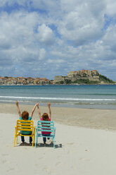 Corsica, Calvi, two children in beach chairs at beach - LBF001158