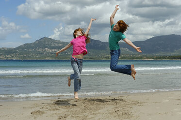 France, Corsica , Calvi, two children jumping in the air on the beach - LBF001156