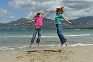 France, Corsica , Calvi, two children jumping in the air on the beach - LBF001155