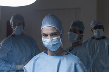 Portrait of surgeon wearing mask with team in background - ZEF007382