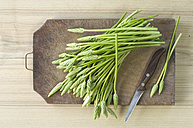 Wild asparagus and kitchen knife on wooden board - ASF005660