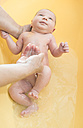 Senior woman bathing newborn baby - DEGF000483