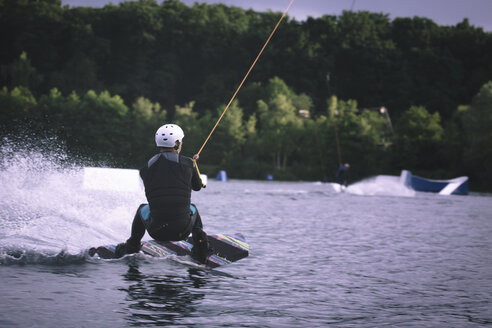 Back view of young man wakeboarding - MADF000505