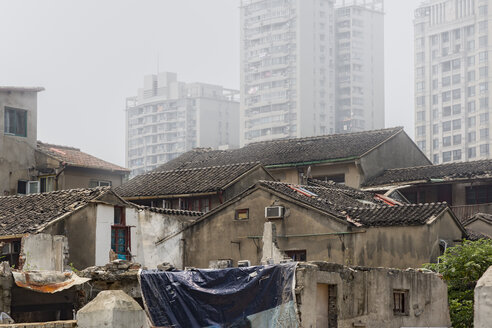 China, Shanghai, small old houses, modern highrises in the background - NKF000340