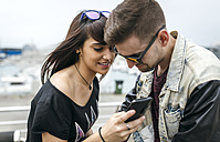 Spain, Gijon, young couple looking at pictures on smartphone - MGOF000406