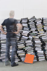Man standing in front of pile of office files - ASF005670