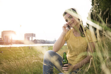 Germany, Cologne, young woman with beer bottle sitting on a meadow near Rhine River telephoning - RIBF000146