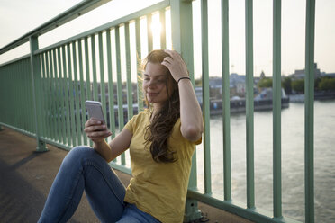 Germany, Cologne, young woman with smartphone sitting on Rhine Bridge - RIBF000147