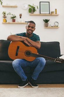 Portrait of smiling man sittining on a couch with guitar - EBSF000850