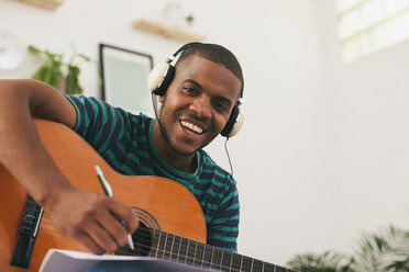 Portrait of smiling man with guitar hearing music with headphones - EBSF000855