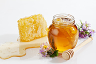 Glass of honey, honeycomb, honey spoon and wild flowers - CSF026024