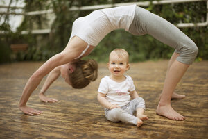 Woman doing yoga exercise while  baby watching her - ABF000631