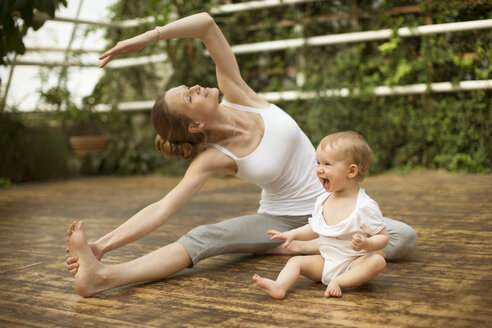 Woman doing yoga exercise while  baby having fun - ABF000633