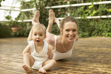 Portrait of baby sitting in front of mother doing yoga exercise - ABF000637
