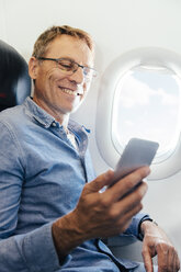 Mature man sitting on an airplane looking at his smartphone - MFF001984