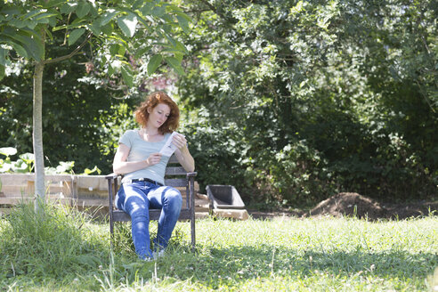 Young woman reading in garden - SGF001819