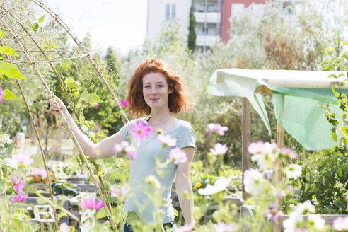 Young woman gardening, urban gardening - SGF001830
