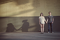 Teenage couple standing hand in hand in front of a wall - MMFF000968