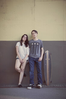Teenage couple and longboard leaning on a wall - MMFF000970