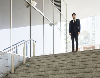 Portrait of young businessman standing at the top of the stairs - PASF000009