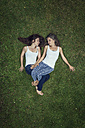 Two sisters lying on a meadow with closed eyes - MW000097