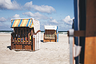 Germany, Mecklenburg-Western Pomerania, Warnemuende, closed hooded beach chairs on the beach - ASCF000296