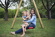 Mother sitting with her two little children on a swing in the garden - MW000094