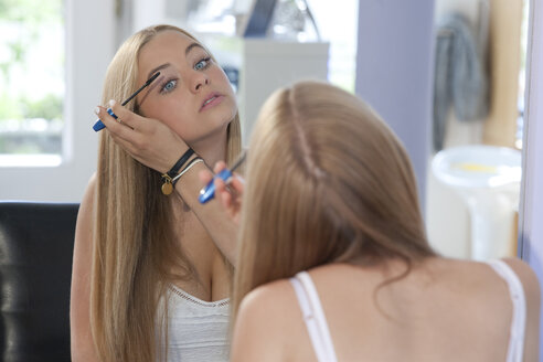 Mirror image of teenage girl applying mascara - TMF000021