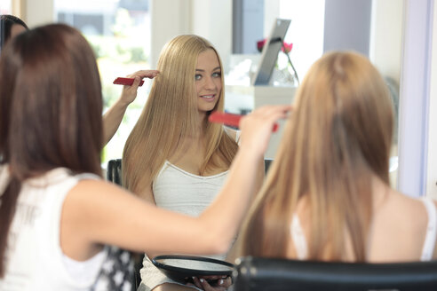 Mirror image of teenage girl at hair salon - TMF000023