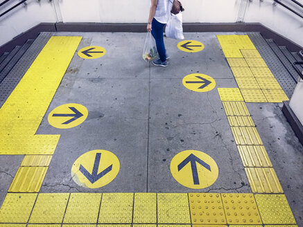 Japan, yellow arrow signs at metro station - FL001175