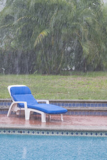 Mexico, Nayarit, heavy summer rain in residential backyard with swimming pool - ABAF001870