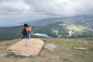 Bulgaria, Rila Mountains, back view of senior woman taking photos with smartphone - DEGF000492