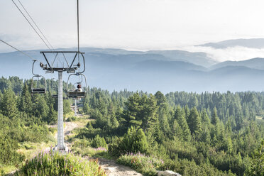 Bulgaria, Rila Mountains, senior woman using chairlift - DEGF000493