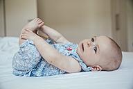 Baby girl lying on her back on bed - MFF001967