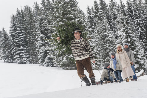 Austria, Altenmarkt-Zauchensee, man with Christmas tree and family together in winter forest - HHF005375