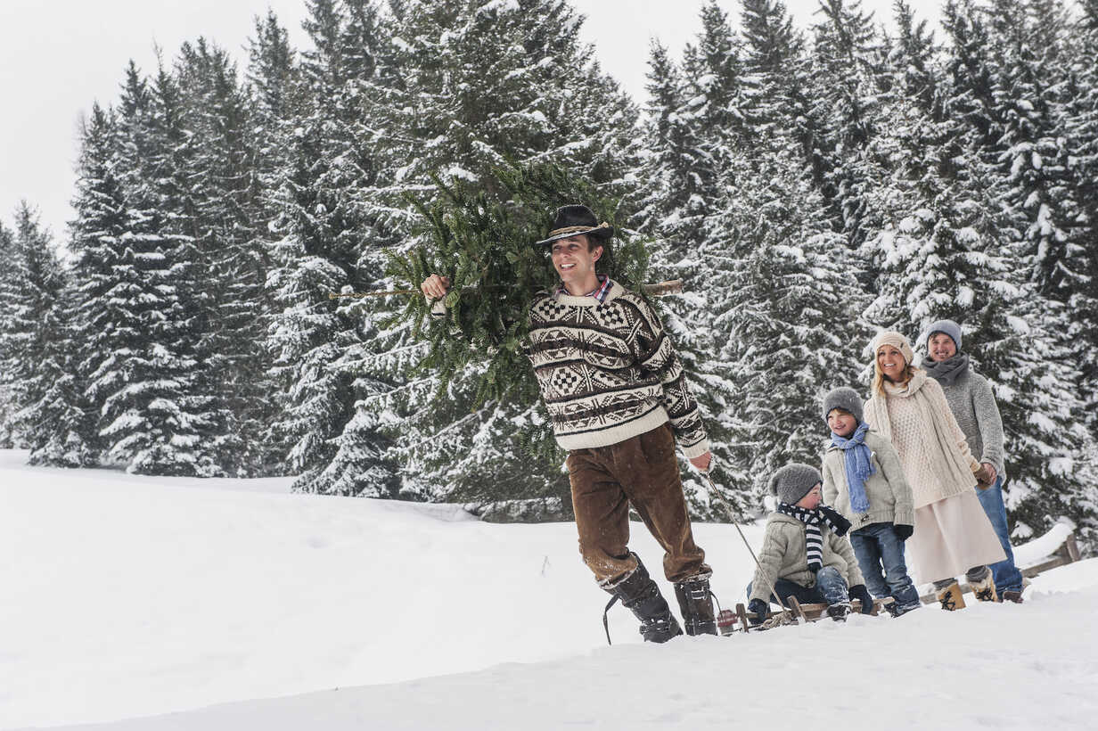 Austria, Altenmarkt-Zauchensee, man with Christmas tree and family together in winter forest - HHF005375 - Hans Huber/Westend61