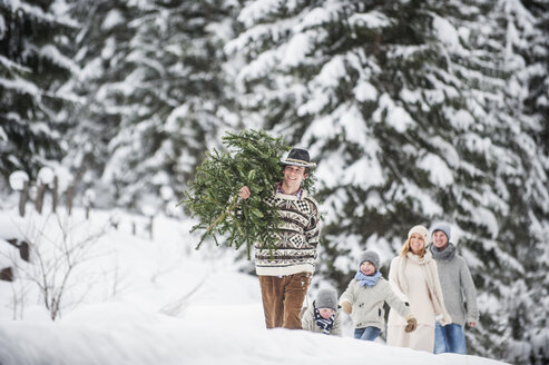 Austria, Altenmarkt-Zauchensee, man with Christmas tree and family together in winter forest - HHF005377