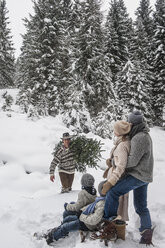 Austria, Altenmarkt-Zauchensee, man with Christmas tree and family together in winter forest - HHF005384