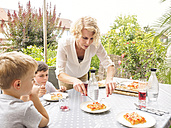 Mother and her two sons eating pizza together on the terrace - LAF001459