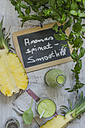 Glass and bottle of spinach pineapple smoothie and chalkboard - ODF001202