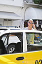 Mexico, Puerto Vallarta, tourist entering taxi while telephoning with smartphone - ABAF001889