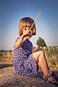 Portrait of little girl sitting on straw bale - LVF003760
