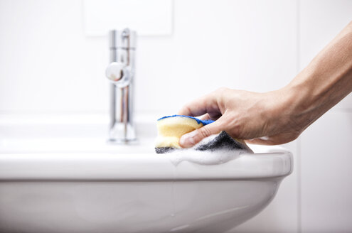 Woman cleaning bathroom sink with sponge - MFRF000340