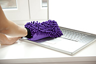 Woman cleansing laptop on windowsill - MFRF000372