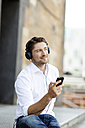 Portrait of smiling man hearing music with MP3 Player and headphones - PESF000006