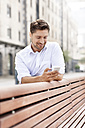 Portrait of smiling man leaning on wooden bench while looking at his smartphone - PESF000039