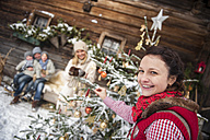 Austria, Altenmarkt-Zauchensee, portrait of smiling woman decorating Christmas tree in front of farmhouse - HHF005394