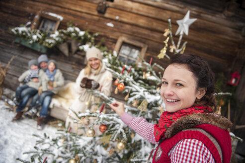 Austria, Altenmarkt-Zauchensee, portrait of smiling woman decorating Christmas tree in front of farmhouse - HHF005394