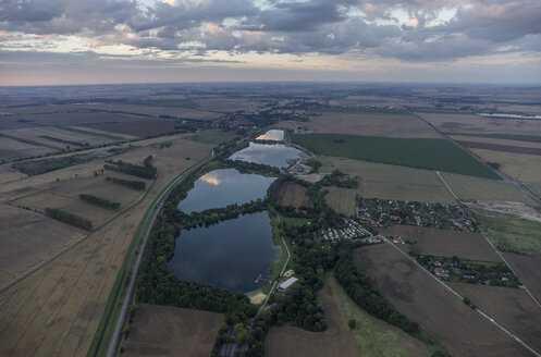 Germany, Wegeleben, aerial view of water-filled gravel pit in the evening - PVCF000567